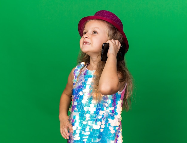 Smiling little blonde girl with purple party hat talking on phone looking at side isolated on green wall with copy space