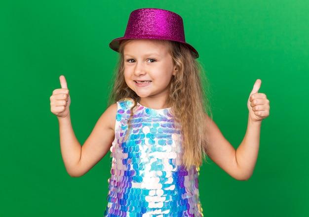 Sorridente bambina bionda con viola party hat sfogliando isolato sulla parete verde con spazio di copia