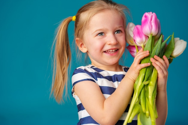 Smiling little blonde girl with tulips bouquet against blue background
