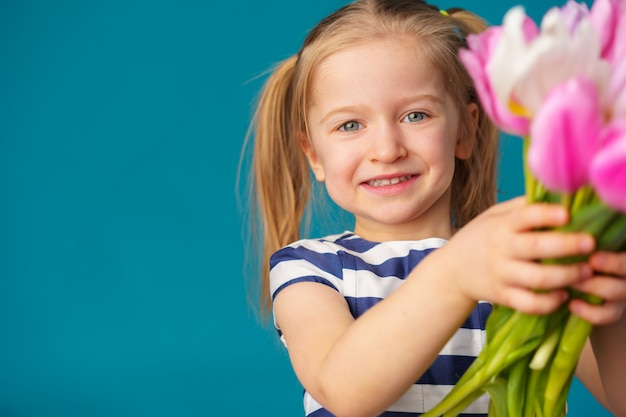 Smiling little blonde girl with tulips bouquet