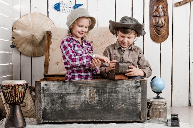 Улыбающийся маленький мальчик и девочка открывает сокровища