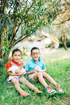 웃고 있는 어린 소년과 소녀는 녹색 덤불 아래 정원의 풀밭에 앉아 흰색을 들고 있다
