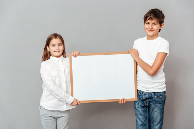 웃는 어린 소년과 소녀 서 빈 화이트 보드를 들고