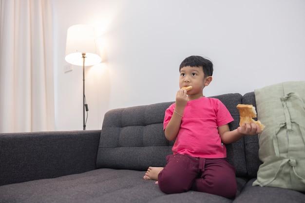 Улыбающийся маленький мальчик ест хлеб и смотрит телевизор на удобном диване в гостиной
