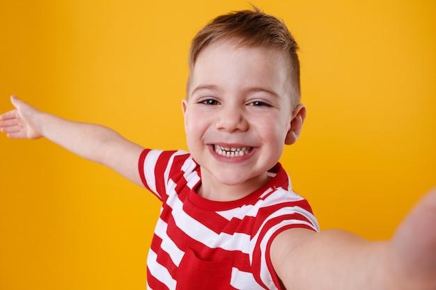 Улыбающийся маленький мальчик держит мобильный телефон и делает селфи