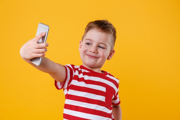 Smiling little boy holding mobile phone and making selfie
