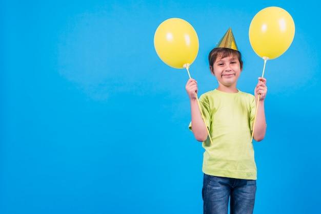 Ragazzino sorridente che tiene i palloni gialli contro il contesto blu con lo spazio della copia per testo
