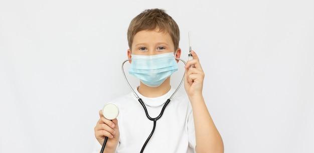 Улыбающийся маленький мальчик в медицинской форме, играя со стетоскопом, изолированным на белом