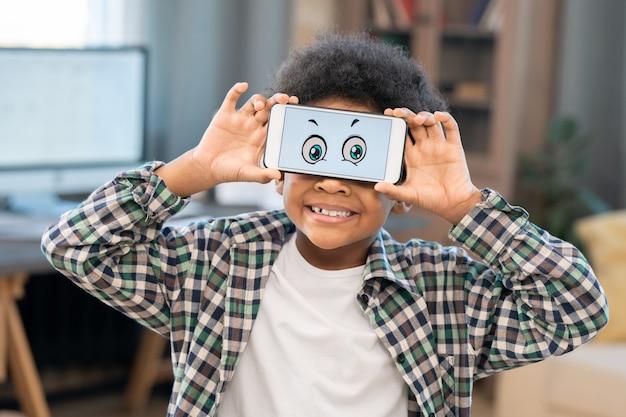 Улыбающийся маленький мальчик в белой футболке и клетчатой рубашке держит смартфон с забавными глазами на экране перед его лицом на фоне домашней обстановки
