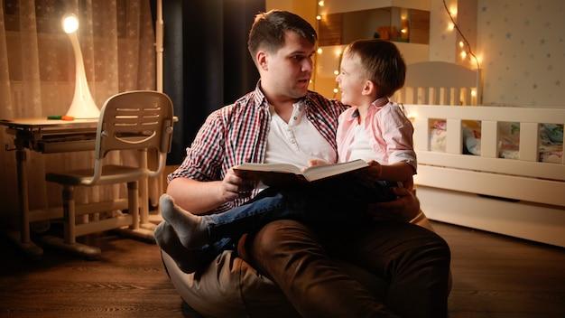 Улыбающийся маленький мальчик, слушающий сказку на ночь, которую отец читает ему по ночам. концепция воспитания детей и семьи, проводящей время вместе в ночное время.