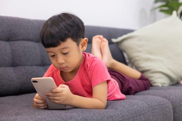 Улыбающийся маленький мальчик смотрит на тачпад, лежа на удобном диване в гостиной