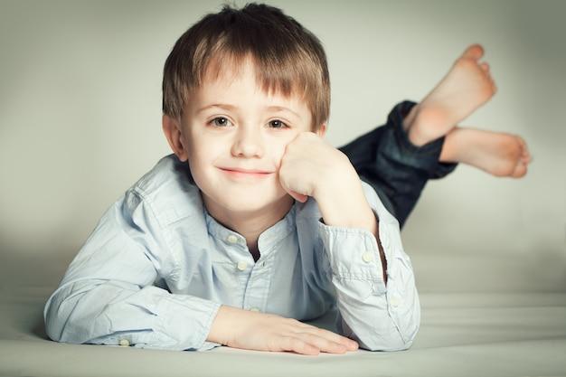 바닥에 누워 웃는 어린 소년