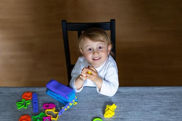 테이블에 색된 플라스 티 신에서 웃는 어린 소년 형