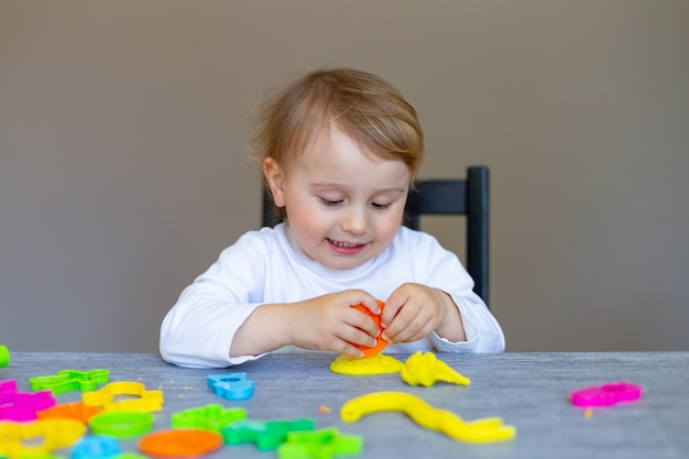Smiling little boy molds from colored plasticine on table