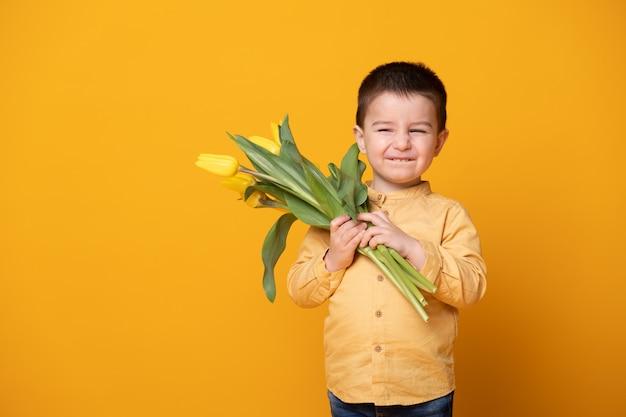 노란색 스튜디오 배경에 웃는 어린 소년. 튤립 꽃 부케와 쾌활 한 행복 한 아이입니다.