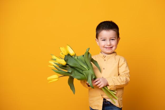 노란색 스튜디오 배경에 웃는 어린 소년