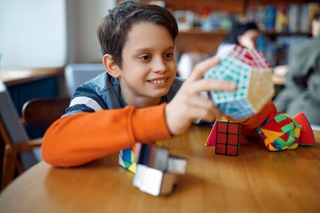 Улыбающийся маленький мальчик играет с красочными кубиками головоломки. игрушка для тренировки мозга и логического мышления, творческой игры, решения сложных задач.