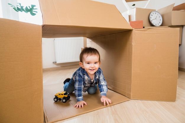 장난감 자동차와 함께 움직이는 골 판지 상자에서 놀고 웃는 어린 소년 프리미엄 사진
