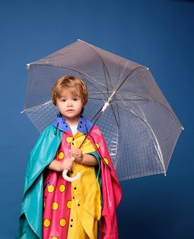 葉で遊んで、カメラを見ている小さな男の子の笑顔。カラフルな傘とレインコートの陽気な男の子。