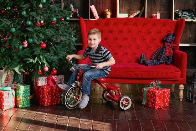 크리스마스 트리가 있는 방에서 자전거를 타고 웃고 있는 어린 소년