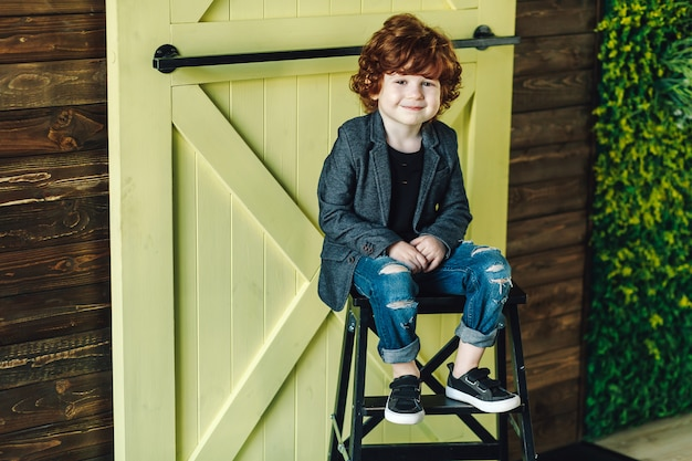 Smiling little boy in ripped jeans sitting on ladder and looking relaxed