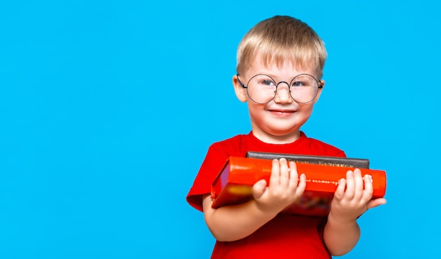 Smiling little boy in round glasses holding a stack of books. education. ready to school