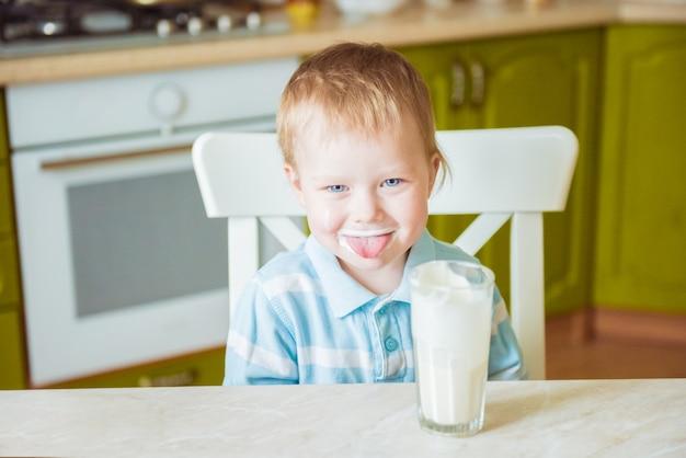 笑みを浮かべて男の子は牛乳で染色された舌を示しています