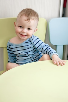 Улыбающийся маленький мальчик сидит за столом