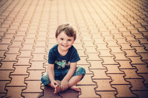 Smiling little boy sitting on the ground