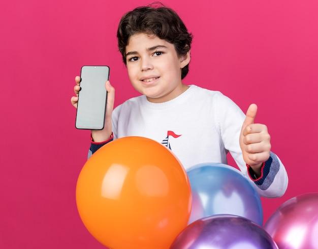 엄지손가락을 보여주는 전화를 들고 풍선 뒤에 서 있는 웃는 어린 소년