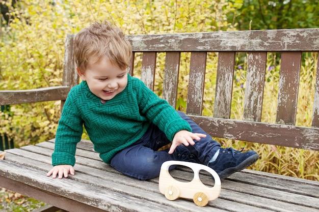 공원에서 산책 웃는 어린 소년. 야외에서 나무 자동차를 가지고 노는 사랑스러운 작은 소년.