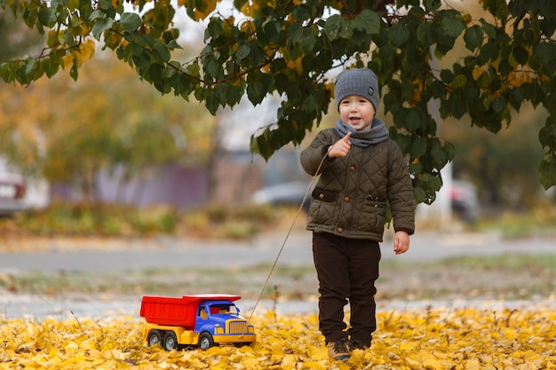 Smiling  little boy walking and playing  with the toy car outdoors in autumn . happy childhood concept. funny child portrait
