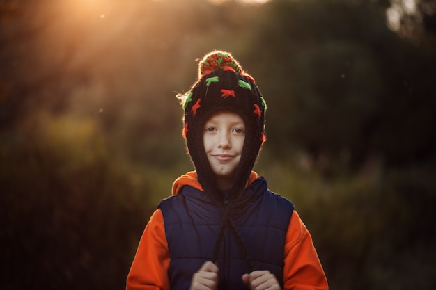 Smiling little boy in warm hat in sunny autumn day.