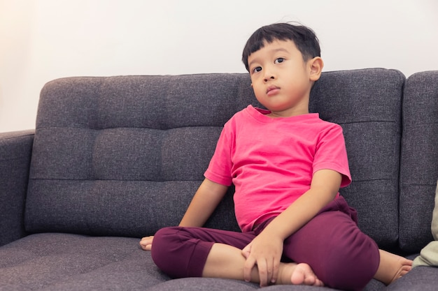 Smiling little boy watch tv and pressing the remote control on comfortable sofa in the living room
