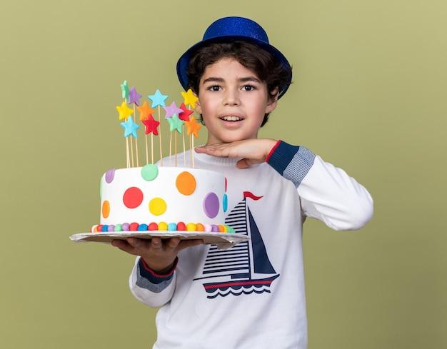 Улыбающийся маленький мальчик в синей партийной шляпе держит торт на оливково-зеленой стене