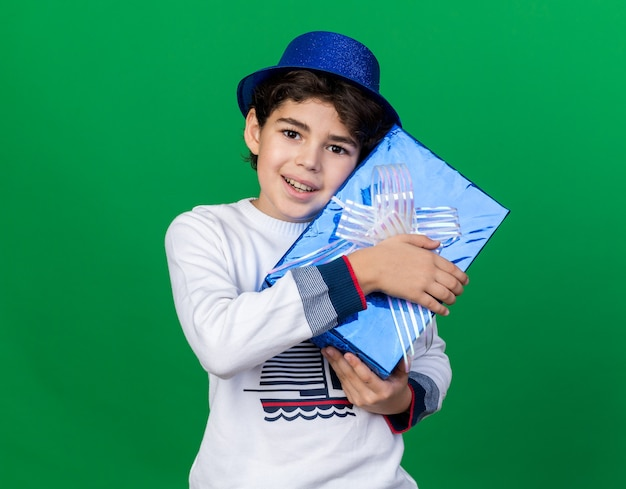 Smiling little boy wearing blue party hat holding gift box around face