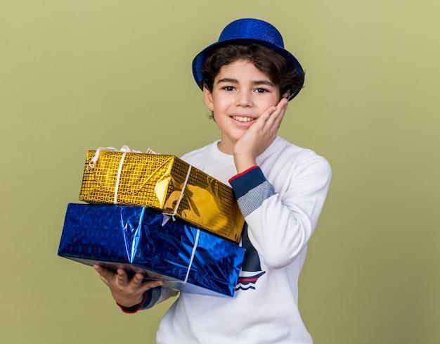 頬に手を置いてギフトボックスを保持している青いパーティーハットを身に着けている小さな男の子の笑顔