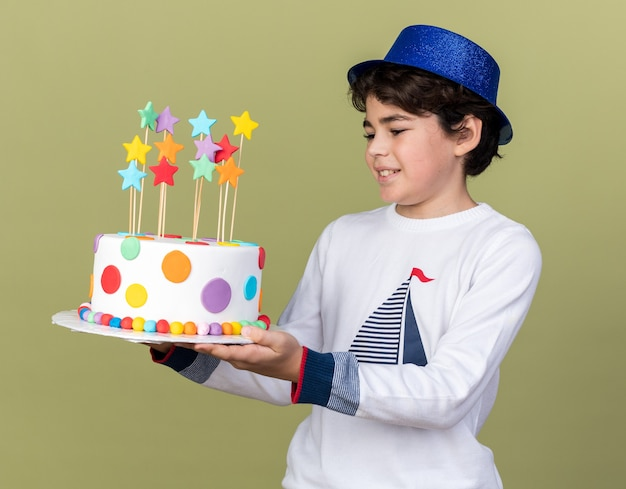 Smiling little boy wearing blue party hat holding and looking at cake