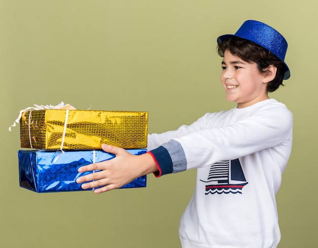 Smiling little boy wearing blue party hat holding out gift boxes at side isolated on olive green wall