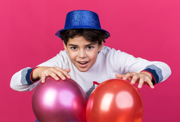 Smiling little boy wearing blue party hat standing behind balloons isolated on pink wall