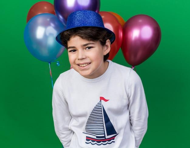 緑の壁に分離された前の風船に立っている青いパーティーハットを身に着けている小さな男の子の笑顔