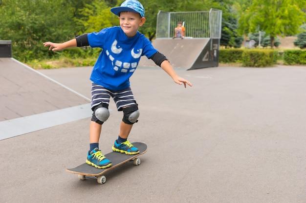 彼は彼の夏休みの自由を楽しんでいる間、スケートパークでスケートボードに沿ってうなり声を上げている小さな男の子の笑顔
