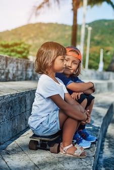 야구 모자를 쓴 웃고 있는 어린 소년이 카메라를 바라보고 밖에 있는 스케이트보드에 여동생과 함께 앉습니다. 태국의 여름 주말.