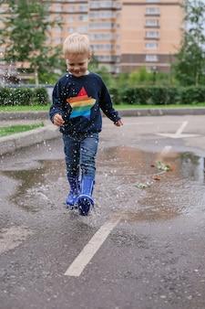 水たまりを歩く青いゴム長靴で金髪の小さな男の子を笑顔