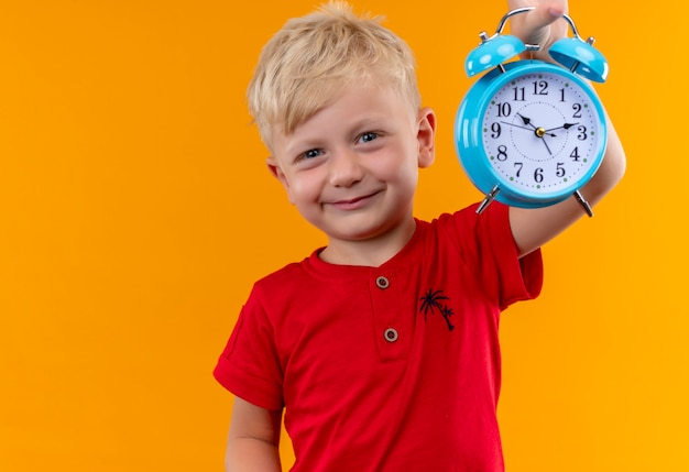 A smiling little boy with blonde hair and blue eyes wearing red t-shirt showing blue alarm clock while looking on a yellow wall