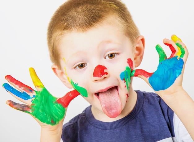 カラフルな絵の具で描かれた手で小さな男の子の笑顔