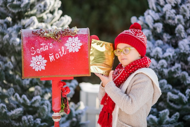 Smiling little boy with red hat and green glasses with his letter near the santa's mailbox