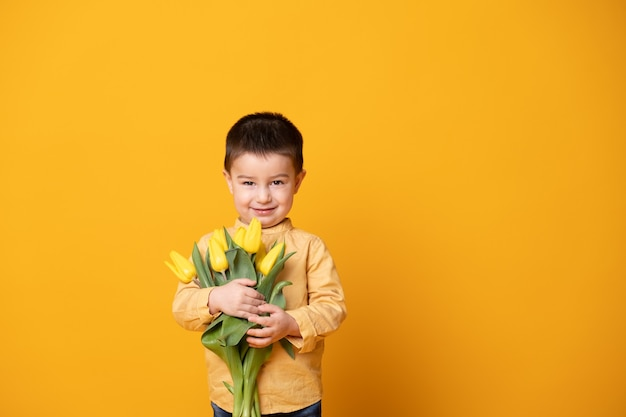 Smiling little boy on yellow studio background. cheerful happy child with tulips flower bouquet.