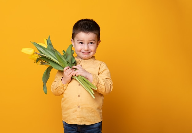 Smiling little boy on yellow studio background