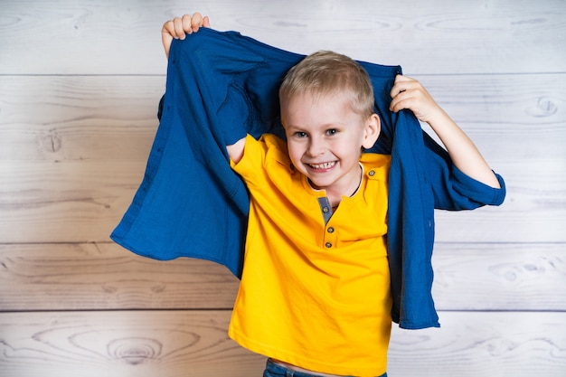 Smiling little boy in yellow t-shirt taking up his blue shirt. portrait of a cheerful child is having fun